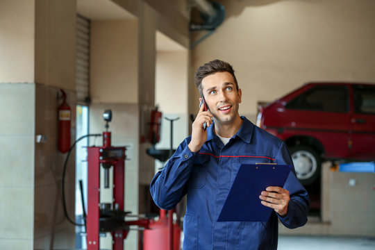 Male mechanic talking by phone in car service center