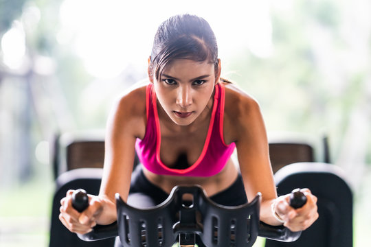 Beautiful Asian woman exercising on stationary cycling machine in indoor fitness gym, determination face. Sport recreational activity, people workout, or healthy lifestyle concept