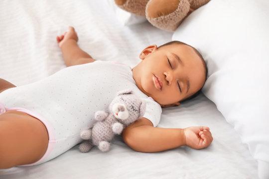 Cute African-American baby sleeping on bed