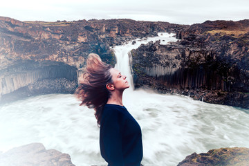 portrait of a beautiful woman with closed eyes and windy hairs against a scenic waterfall in the background