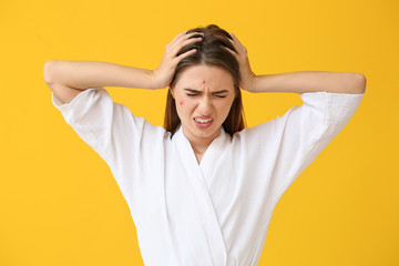 Portrait of stressed young woman with acne problem on color background