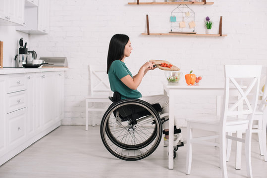 side view of disabled young woman preparing salad while sitting on wheelchair near table