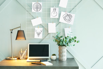 Comfortable workplace with mood board in room