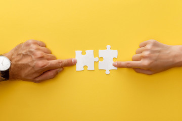 cropped view of woman and man matching pieces of white jigsaw puzzle on yellow background