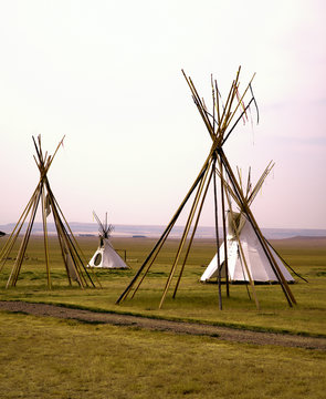 Teepees with and without coverings in late afternoon.