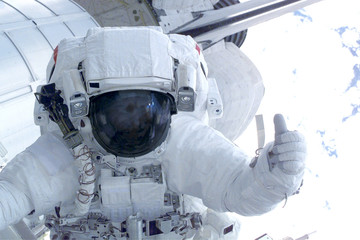 Astronaut on a space station showing thumbs up. Elements of this image were furnished by NASA.