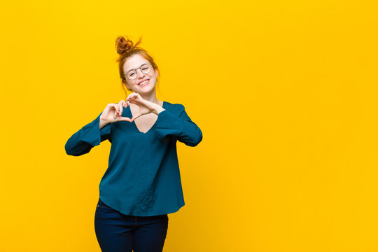 young red head woman smiling and feeling happy, cute, romantic and in love, making heart shape with both hands against orange wall