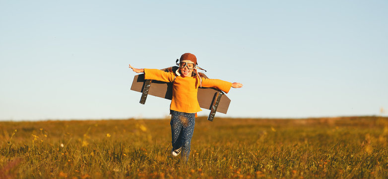 Child pilot aviator with wings of airplane dreams of traveling in summer  at sunset.