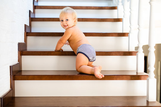 10 months adorable blonde baby development , climbing up stairs at home