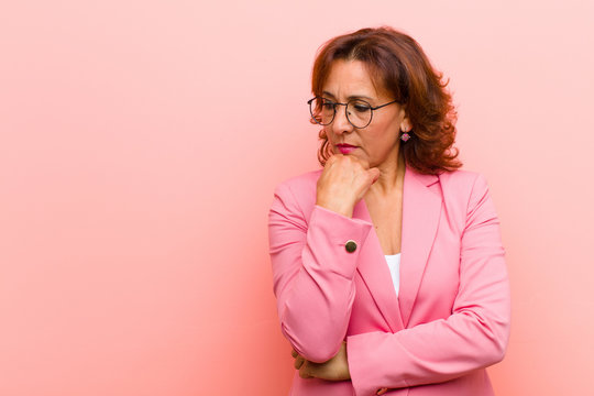 middle age woman feeling serious, thoughtful and concerned, staring sideways with hand pressed against chin against pink wall