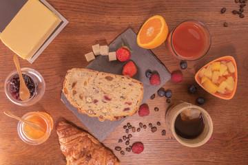 Petit déjeuner varié avec pain aux fruits secs et céréales jus d'orange frais miel et confiture de fraise, beurre thé et fruits rouges et salade de fruits grains de café et croissant