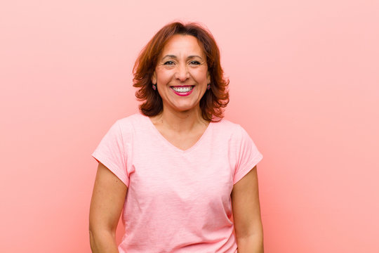 middle age woman looking happy and goofy with a broad, fun, loony smile and eyes wide open against pink wall