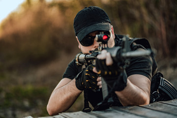 Close-up image of man aiming with sniper rifle.