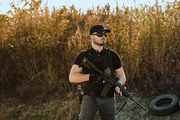 Private security member with shooting rifle outdoors, portrait.