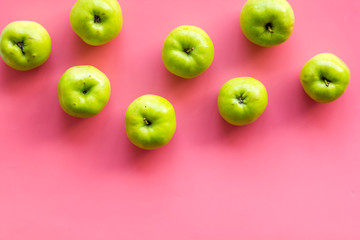 Green apples pattern on pink background top view frame space for text