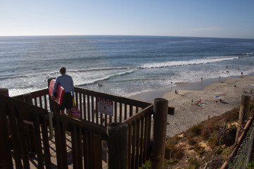 older man with boogie board looking out over ocean and beach