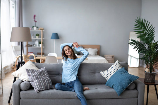 Happy casual beautiful woman sitting on a sofa at home.