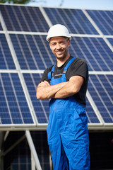 Portrait of smiling successful male engineer technician standing in front of unfinished high exterior solar panel photo voltaic system blue shiny surface.