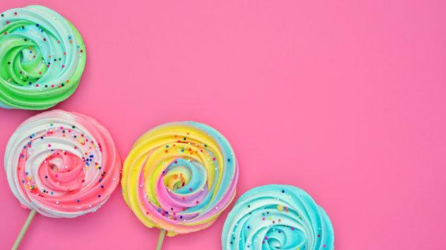 Colorful meringue lollipop on a pink background.