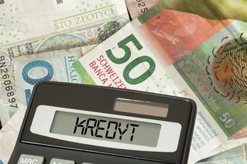 Banknoten Schweizer Franken und polnische Zloty, Taschenrechner und polnisches Wort für Kredit