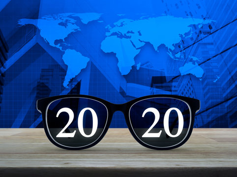 2020 white text with black eye glasses on wooden table over world map, city tower and skyscraper, Business vision happy new year 2020 concept, Elements of this image furnished by NASA
