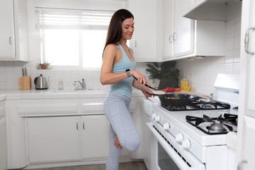 Beautiful healthy fit and toned woman cooking a plant based diet meal in a bright kitchen, after a exercise workout, nutrition and fitness portrait