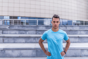 male athlete, in summer city, stands confidently looking, coach controls exercise. Free space for text. Active lifestyle, workout, fitness in fresh air. Motivation for sports. Blue stair t-shirt.
