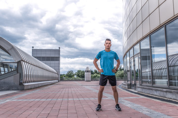 male athlete, summer city, posing full growth, looking confidently, coach controls exercise. Free space text. Active lifestyle workout fitness fresh air. Motivation sports. Sportswear Short T-shirt.