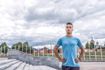 Male athlete poses in morning, coach in summer in spring in city, training on street. Active lifestyle, workout, fitness in fresh air. Motivation for sports. Free space for text.