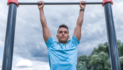 male athlete pulls himself up on bar. In summer spring in city. Active lifestyle, workout, fitness in fresh air. Motivation for sports. Blue t-shirt, cloud background.