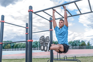 Male athlete, training abdominal muscles, exercise on press, raising legs crossbar. In summer spring in city. Active lifestyle, workout, fitness fresh air. Motivation Blue t-shirt, cloud background.