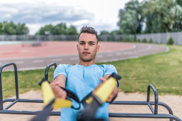Male athlete, loops straps training chest muscles, exercise arms shoulders. In summer spring city. Active lifestyle, workout, fitness fresh air. Motivation for sports. Background sports field.