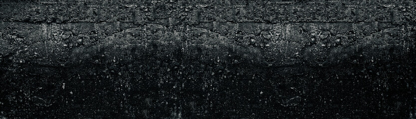 Dark grey wide rough concrete wall texture. Black weathered cement surface widescreen background. Gloomy grunge long panoramic backdrop