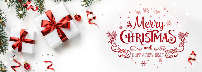 Merry Christmas text on white background with gift boxes, fir branches, red decoration. Xmas and New Year greeting card, bokeh, light. Flat lay, top view, winter holiday, wide compositon