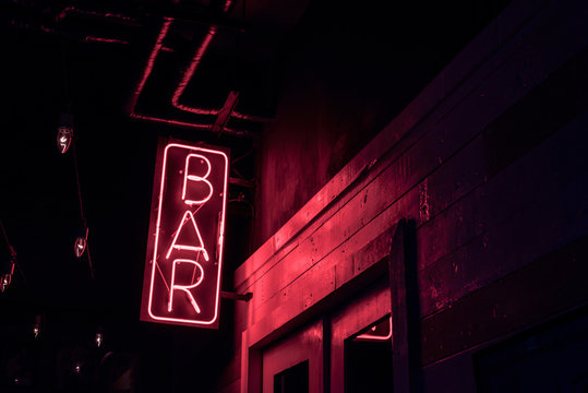 neon BAR sign lights up the doorway of a drinking establishment at night
