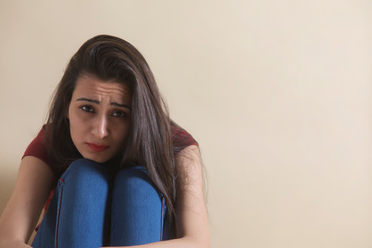Young girl sitting alone in distress