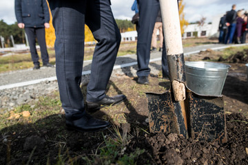man in a business suit with a shovel plant a new tree