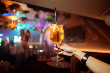The girl is holding a glass of cocktail in her hand Aperol Spritz