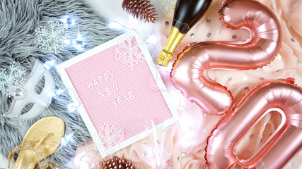 New Year's Eve flatlay hygge style overhead with rose gold 20 balloons and letter board spelling Happy New Year greeting.