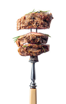 Beef steak on a fork isolated on a white background.