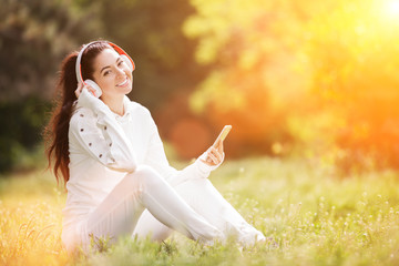 Happy woman with headphones relaxing in the autumn park. Beauty nature scene with colorful background. Fashion woman enjoying the music from her mobile phone at fall. Outdoor lifestyle