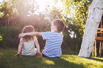 children hugging in the garden at the sunset. brother with  his little sister outdoor back