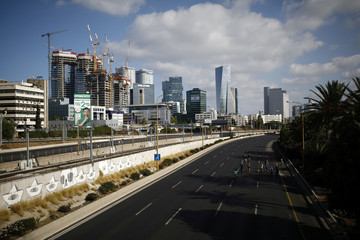 People ride their bicycles on an empty highway during the Jewish holiday of Yom Kippur in Tel Aviv, Israel