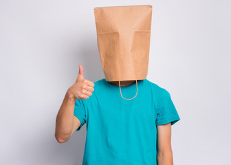 Fototapete - Portrait of teen boy with paper bag over head making thumb up gesture. Teenager cover head with bag showing success sign posing in studio. Child pulling paper bag over head.