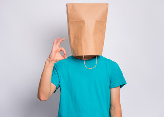 Fototapete - Portrait of teen boy with paper bag over head making Ok gesture. Teenager cover head with bag showing okay sign posing in studio. Child pulling paper bag over head.