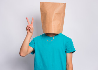 Fototapete - Portrait of teen boy with paper bag over head making Victory gesture. Teenager cover head with bag showing victory sign posing in studio. Child pulling paper bag over head.