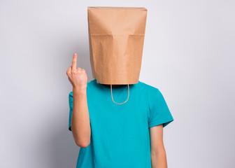 Fototapete - Portrait of teen boy with paper bag over head making middle finger. Teenager cover head with bag showing bad gesture posing in studio. Child pulling paper bag over head doing obscene sign.