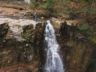 man standing on the cliff looking at waterfall autumn time