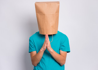 Fototapete - Portrait of teen boy praying, with paper bag over head, on gray background. Child with hands folded in prayer hoping for better. Teenager asking God for good luck, success or forgiveness.