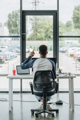 back view of young african american programmer showing idea sign while sitting at workplace in office